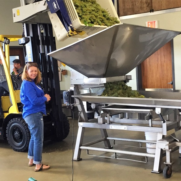 Winemaker Luisa smiles as we work out the kinks to the first chardonnay grape destemming